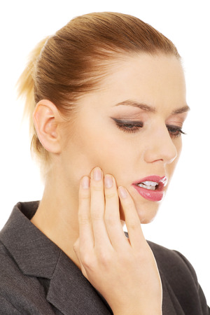 suffering: Young businesswoman suffering from tooth ache.