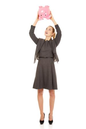 Happy business woman shaking a piggybank. photo