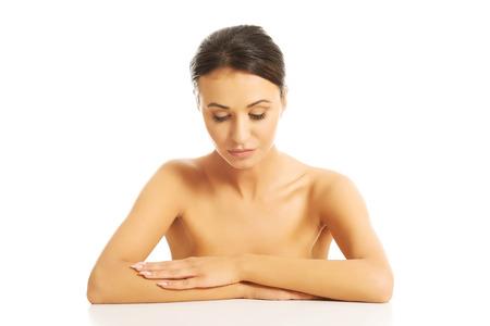 topless: Belle femme aux seins nus assis au bureau, les bras crois�s Banque d'images