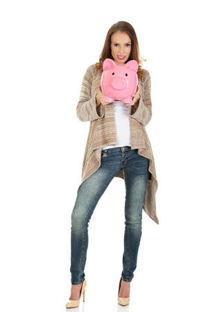 piggybank: Beautiful casual woman holding piggy-bank.