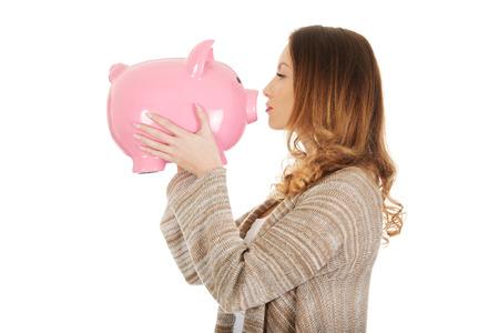 piggybank: Beautiful casual woman kissing piggy-bank.