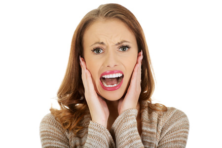 woman shouting: Beautiful casual scared woman screaming. Stock Photo