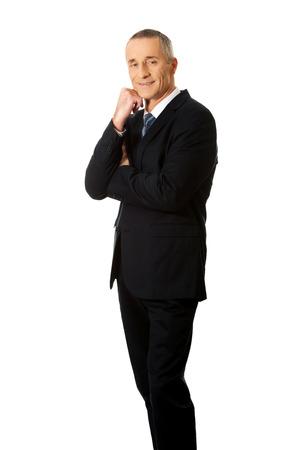 chin: Happy mature businessman with hand under chin.