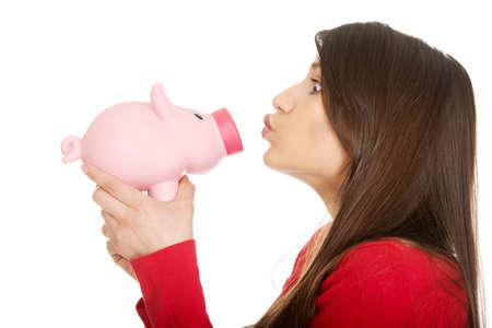 beso: Estudiante mujer feliz que besa a una hucha.