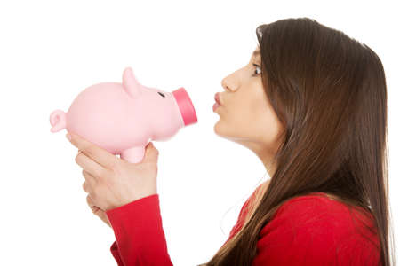 kissing: Happy student woman  kissing a piggybank.