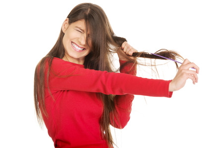 Painful woman combing her tangled hair. Stock Photo
