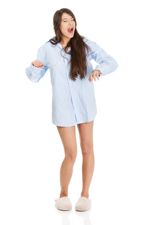 big shirt: Young morning yawning woman in big shirt and slippers.