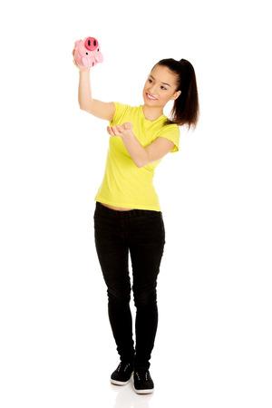 Happy teenage woman shaking piggybank. photo