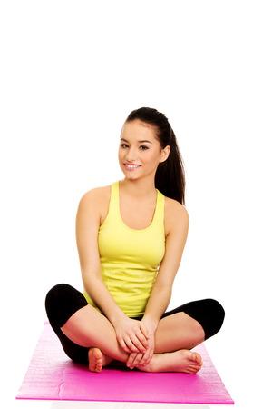 legged: Fitness woman sitting cross legged on exercise mat.