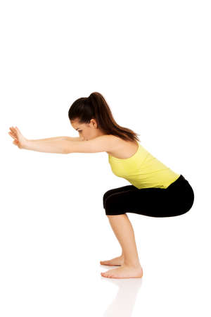 squats: Attractive fitness woman performs squats. Stock Photo