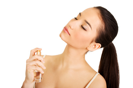 parfume: Young beautiful woman applying parfume.