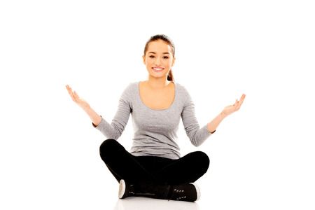 cross legged: Young woman sitting cross legged with open hands.