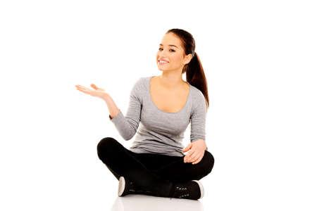 cross legged: Young woman sitting cross legged with open hand. Stock Photo