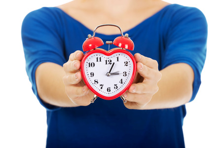 alarmclock: Young happy woman holding alarmclock. Stock Photo
