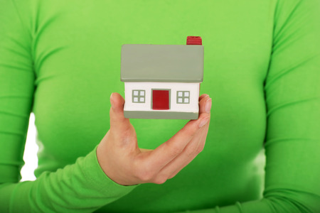 first time buyer: Young woman holding small house. Stock Photo