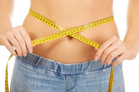 Slim caucasian woman measuring her waist. photo