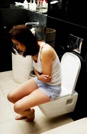 constipated: Beautiful caucasian woman is sitting on the toilet. Stock Photo