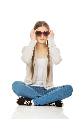 one teenager: Funny teen woman sitting wearing sunglasses.