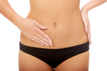 menstruation period: Woman in underwear touching her slim belly. Stock Photo