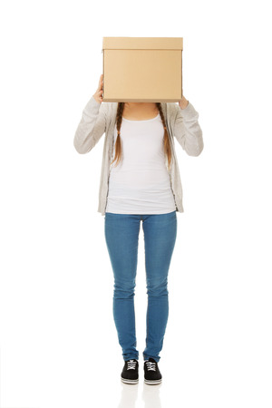 covering face: Teen woman covering face with a carton box.