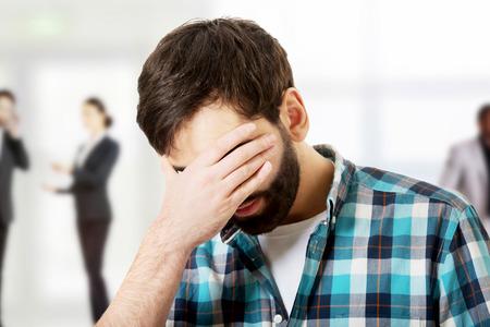 cara triste: Hombre joven trastornado que cubre su rostro.