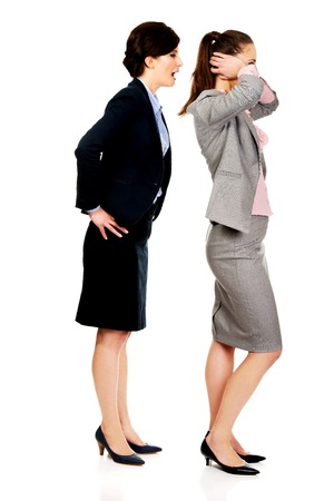 25 30 years women: Businesswoman covering ears from her angry partner.