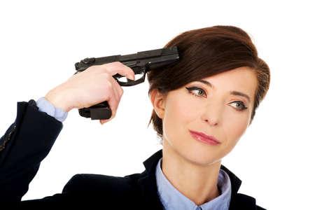 holding gun to head: Despair businesswoman holding a gun near head.