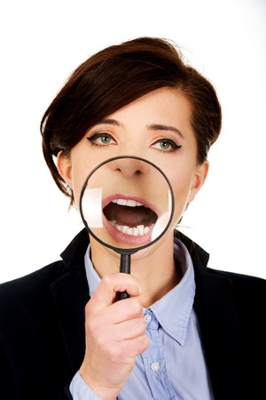 Funny businesswoman with magnyfing glass on teeth. photo