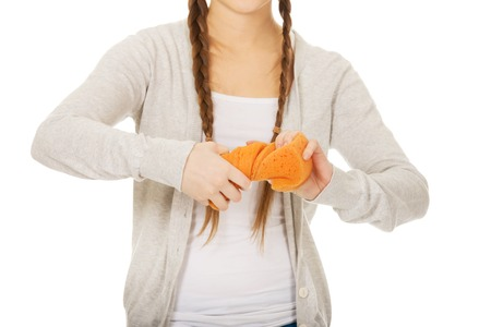 squeezing: Teen woman squeezing a sponge. Stock Photo