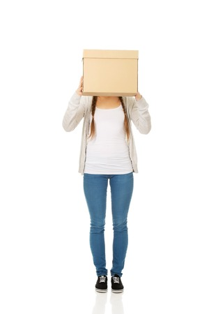 covering the face: Teen woman covering face with a carton box.