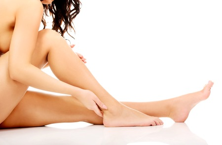 naked female body: Spa woman touching her slim legs.