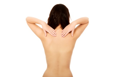 topless brunette: Beautiful topless woman touching her back. Stock Photo