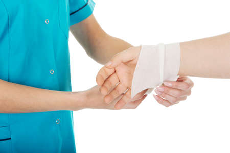 medical background: Caucasian woman doctor bandaging female hand