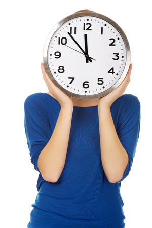 covering the face: Woman covering face with a clock.