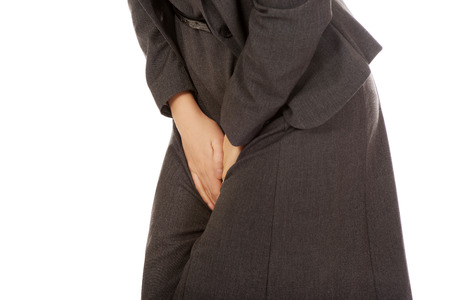 crotch: Businesswoman holding her painful crotch. Stock Photo