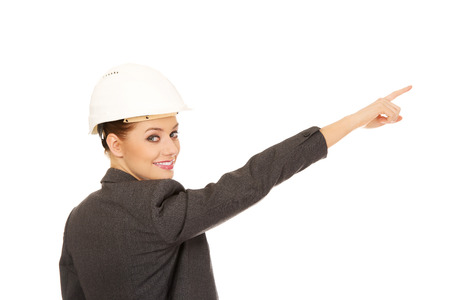 hard hat: Beautiful businesswoman in hard hat pointing up. Stock Photo