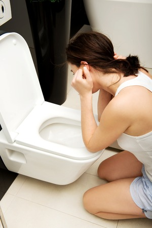Beautiful adult woman vomiting in toilet. photo