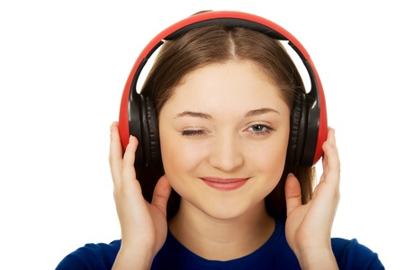 Teenage woman with headphones blinks eye. photo