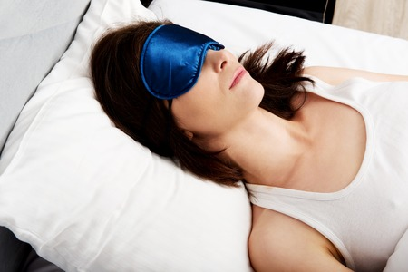 sleep: Beautiful woman sleeping in bed with eyes band. Stock Photo