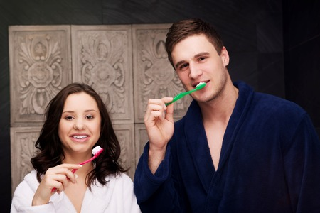 couple bathroom: Beautiful couple in the bathroom brushing teeth. Stock Photo
