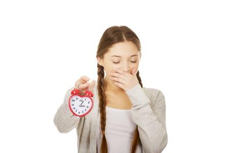 alarmclock: Exhausted teenage woman with alarmclock.