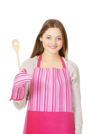 kitchen apron: Teen woman in kitchen apron holding wooden spoon. Stock Photo