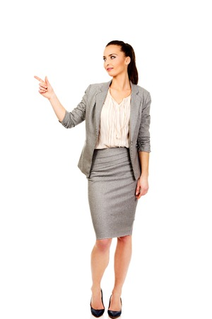 pointing up: Beautiful confident businesswoman pointing up. Stock Photo