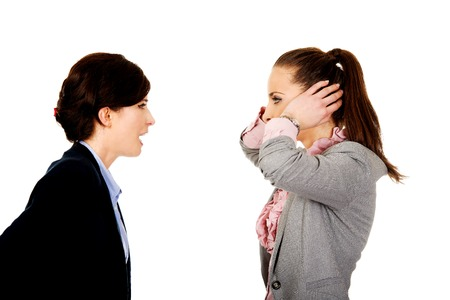 communication breakdown: Businesswoman covering ears from her angry partner.