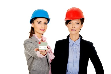 executive helmet: Two attractive architects women with house model.