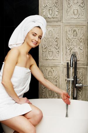woman in bath: Beautiful woman pours water in a bath.