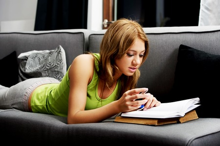 teenage: Young teenage woman learning to exam on a sofa. Stock Photo