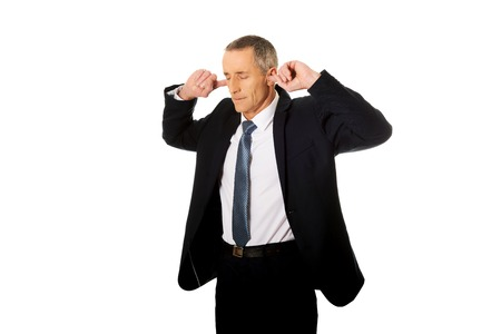 silenced: Mature businessman plugging his ears. Stock Photo