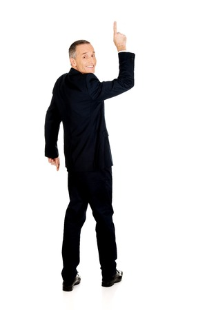 full length: Full length businessman pointing upwards. Stock Photo