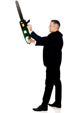 self assured: Furious mature businessman with chainsaw.